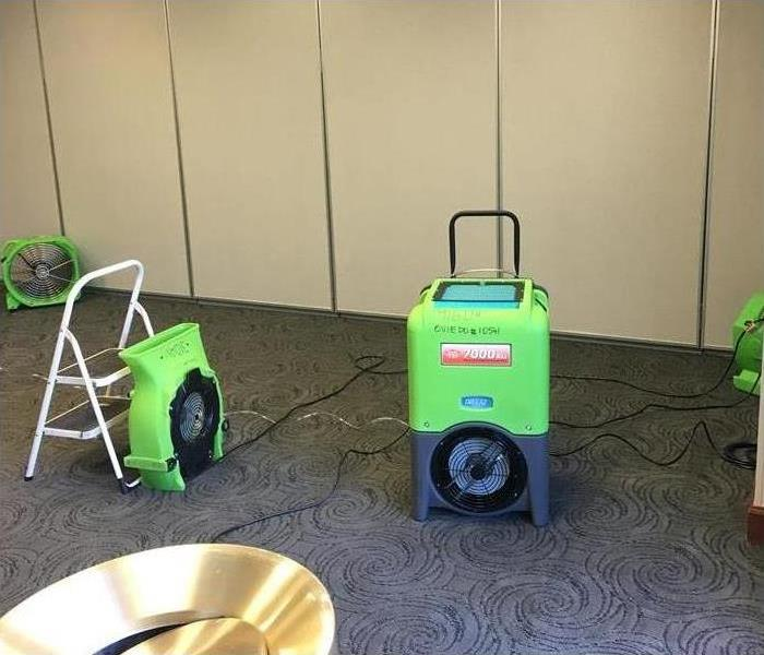 Humidifiers and air movers placed on carpet of a lounge drying up affected area after a water loss